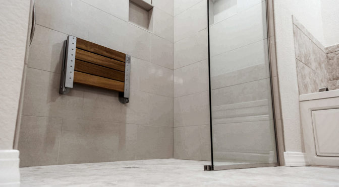 A walk-in shower with wall mounted shower seat