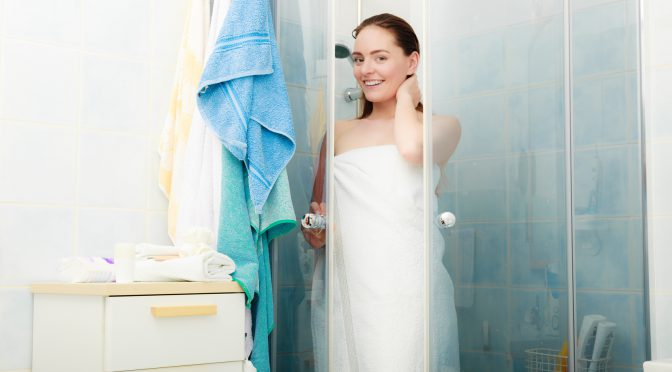 Young lady in a towel exiting the shower enclosures